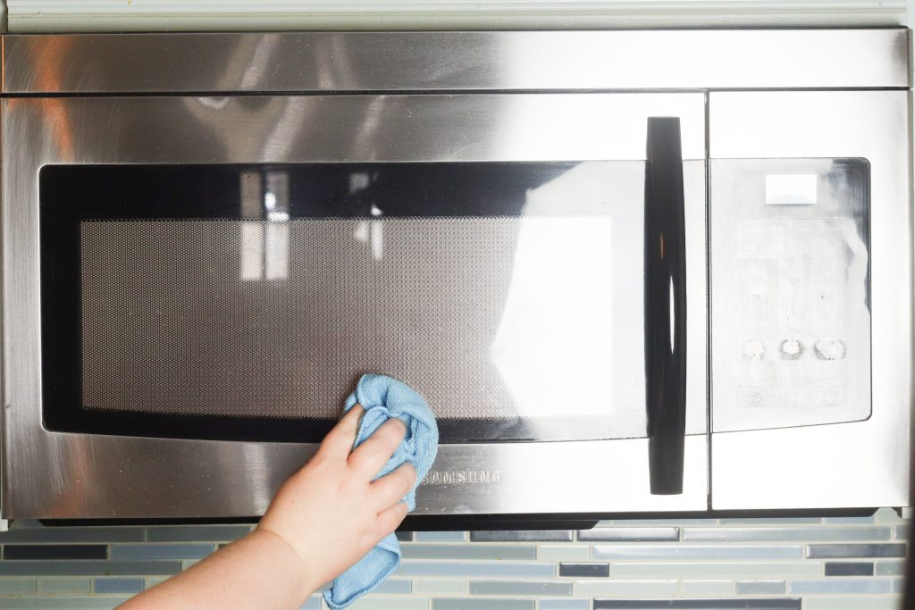 Wiping the outside of a microwave with vinegar